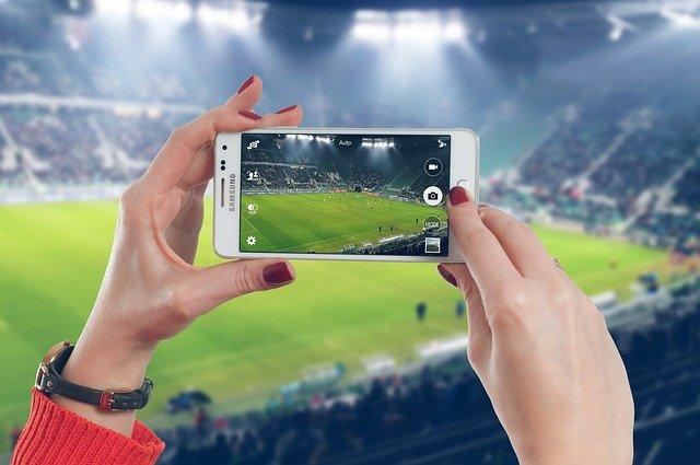 žena s mobilem na stadionu
