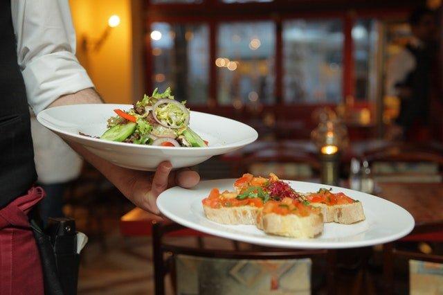 Čašník v reštaurácii nesie taniere s jedlom.jpg