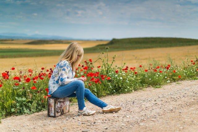 Nahnevaná žena sedí na kufri uprostred cesty.jpg