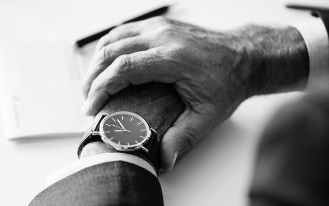 Muž pozerá na hodinky na svojom zápästí.jpg