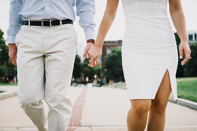 Kráčajúci muž a žena držiaci sa za ruku