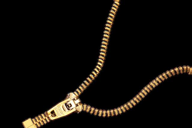 Detail na zlatý rozpnutý zips na bielom podklade.png